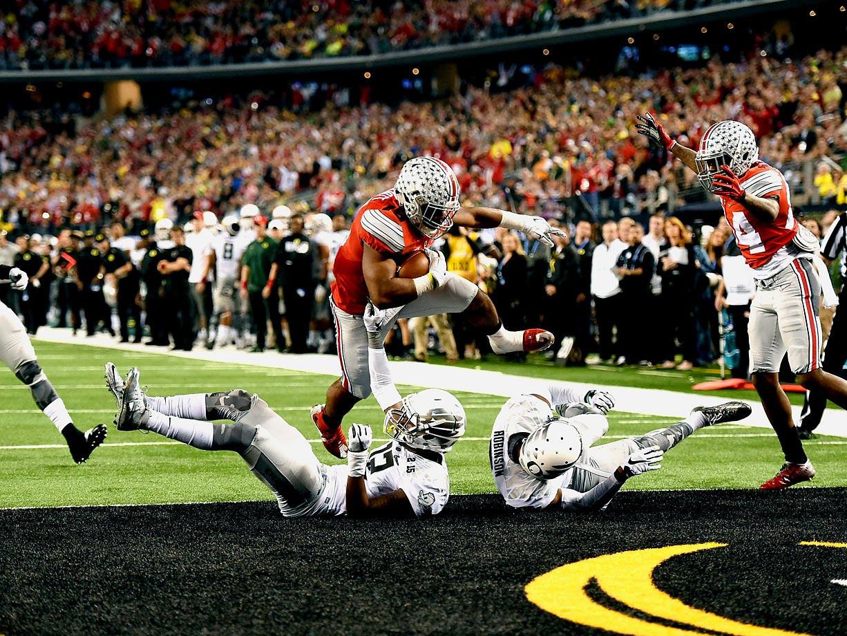 Ohio State running back Ezekiel Elliott runs over two Oregon Ducks for one of his four touchdowns.