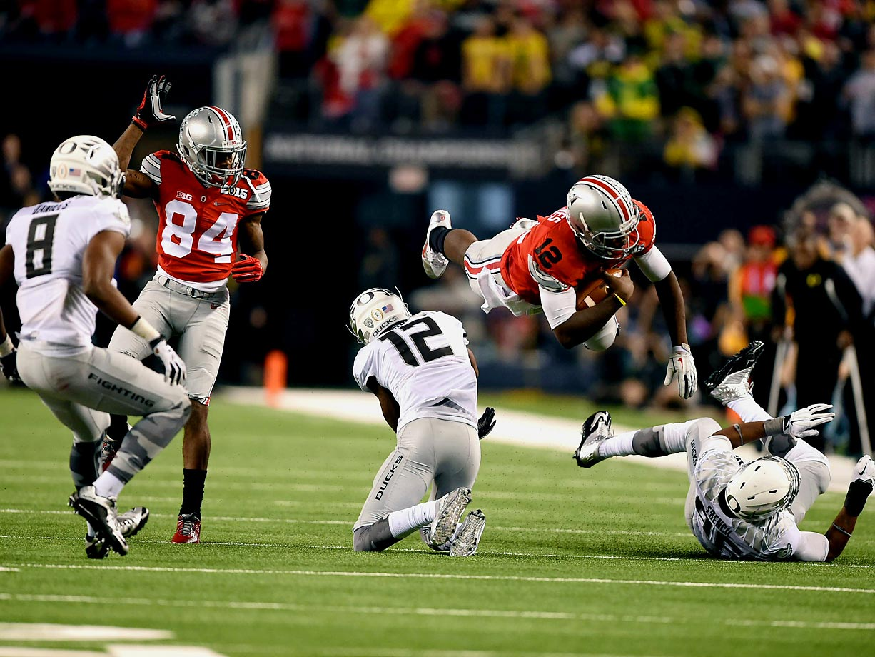 Ohio State quarterback Cardale Jones leaps over two Oregon defenders. Jones ran for 38 yards on 21 carries in the Buckeyes' 42-20 win.