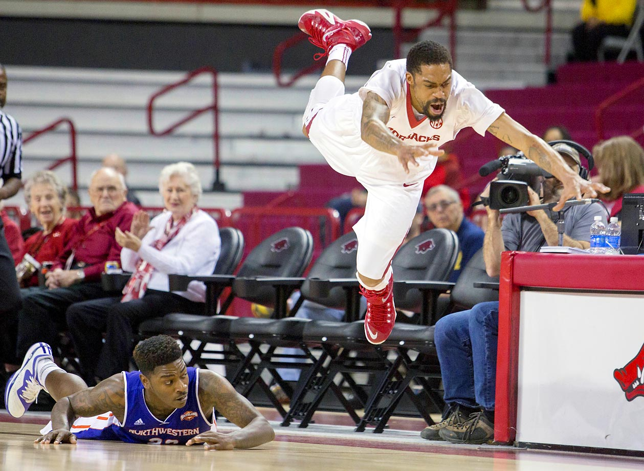 Arkansas guard Rashad Madden dives for a loose ball as Northwestern State guard Zeek Woodley looks on from the floor.