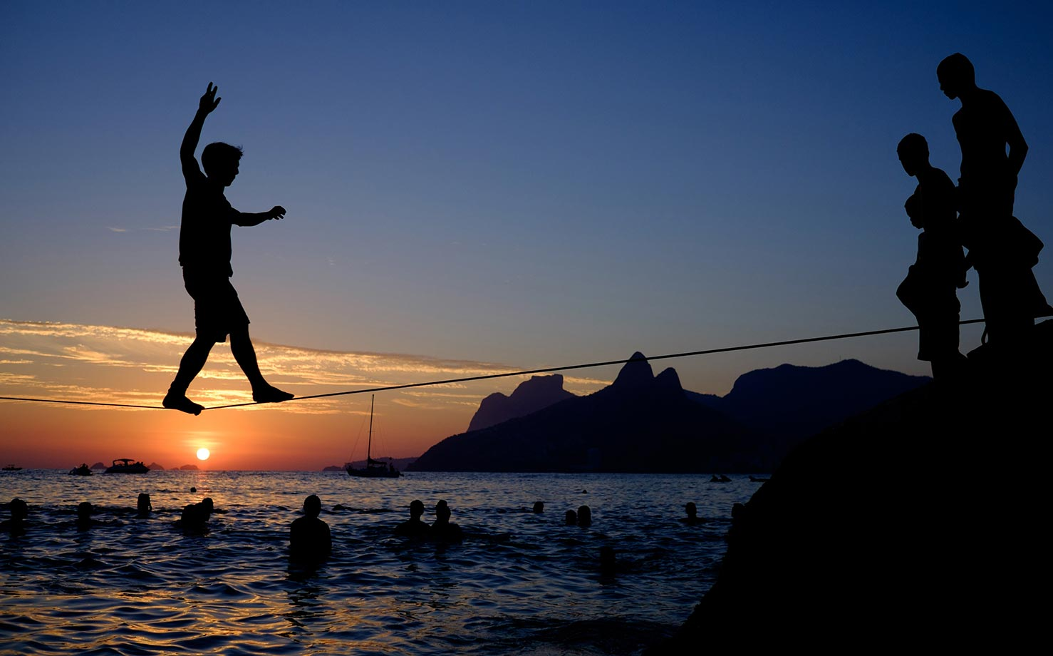 A man crosses on a slickline over the water at Apoador beach in Rio de Janeiro.