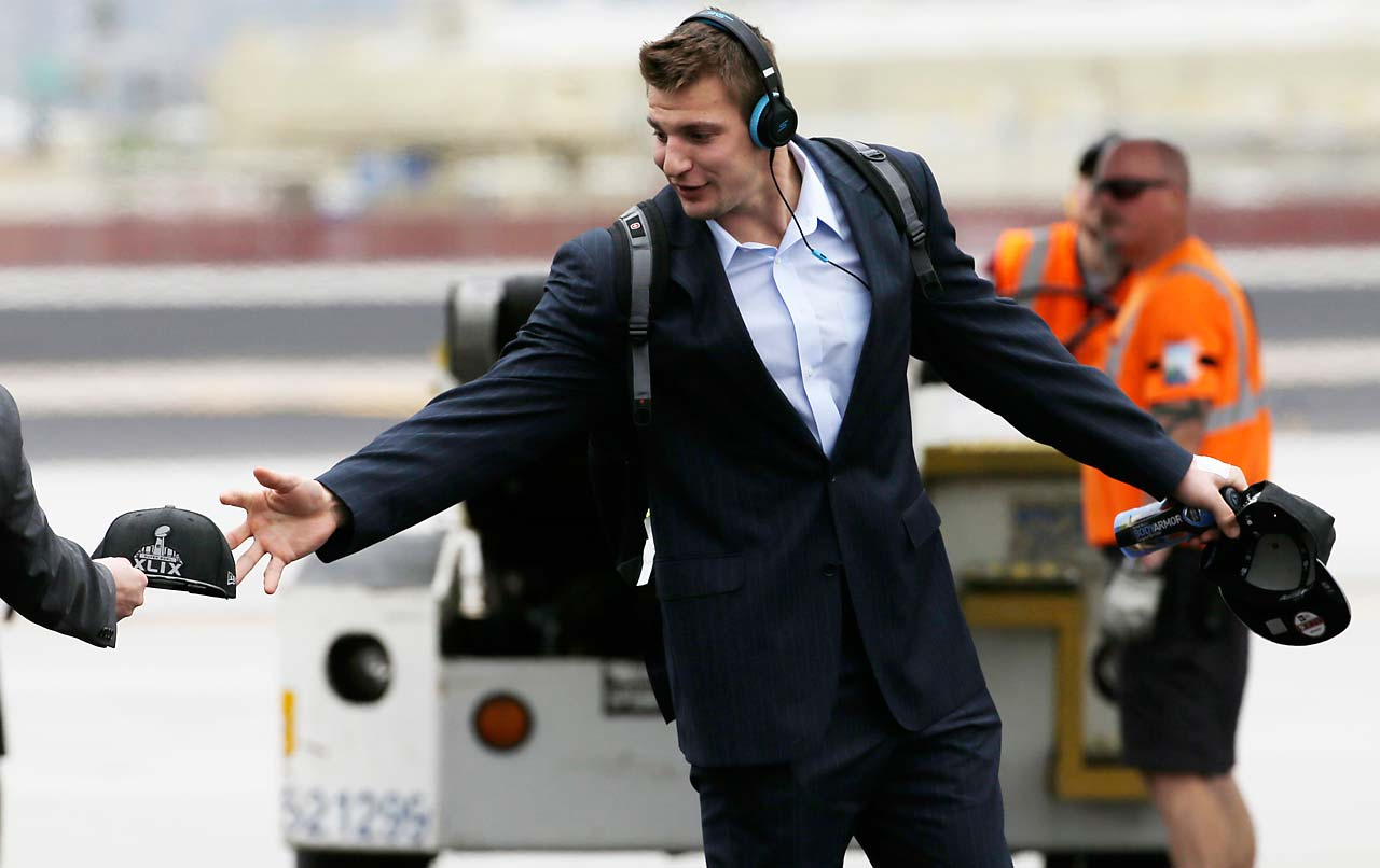 Patriots tight end Rob Gronkowski takes a Super Bowl hat as he arrives at Sky Harbor Airport.