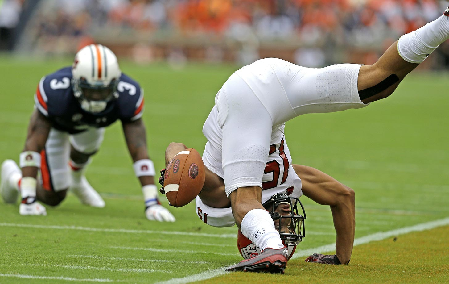 Ruben Gonzalez of Jacksonville State flips over after catching a pass against Auburn.