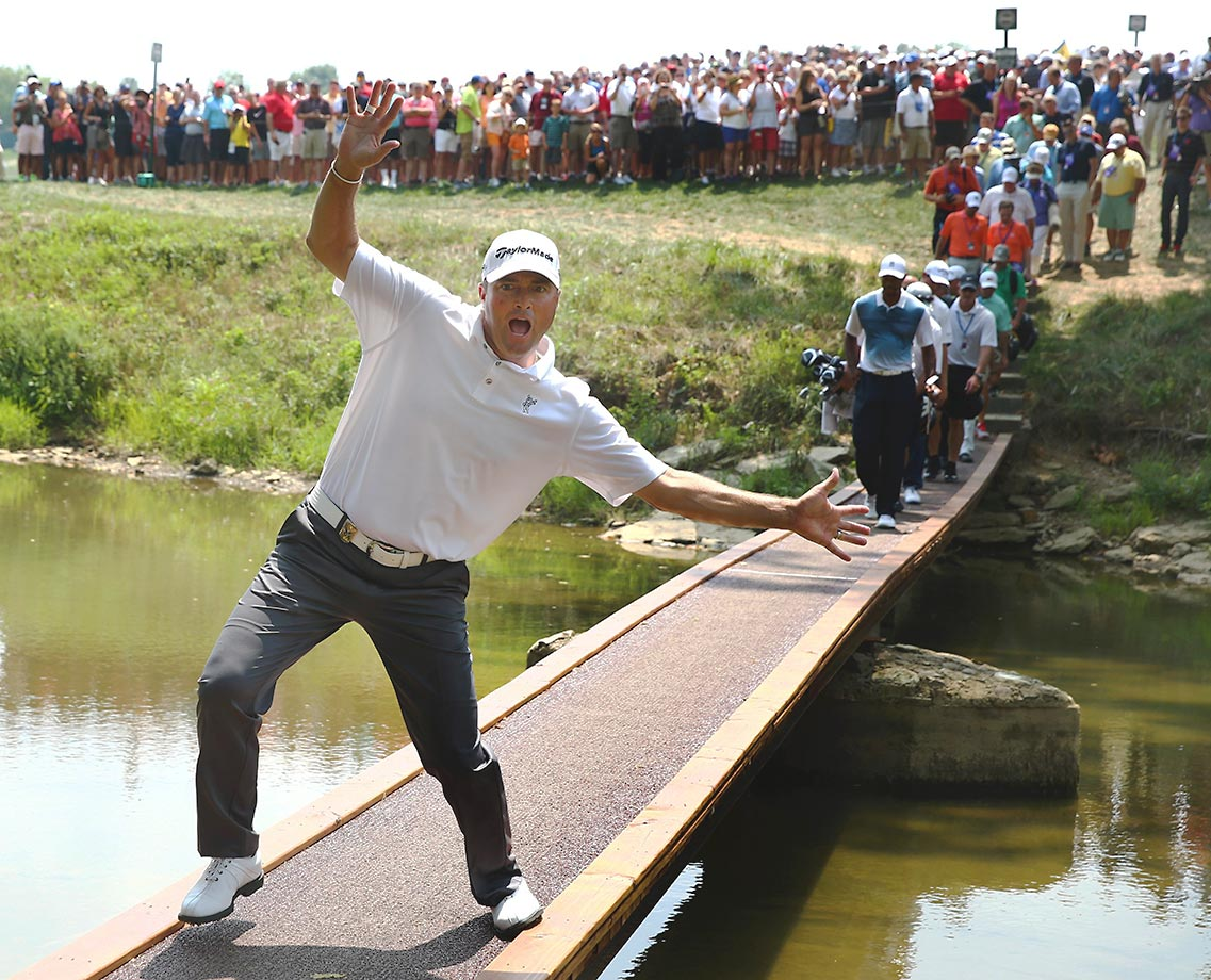 Ryan Palmer of the United States photobombs Tiger Woods as he crosses a bridge during a practice round at the PGA Championship.