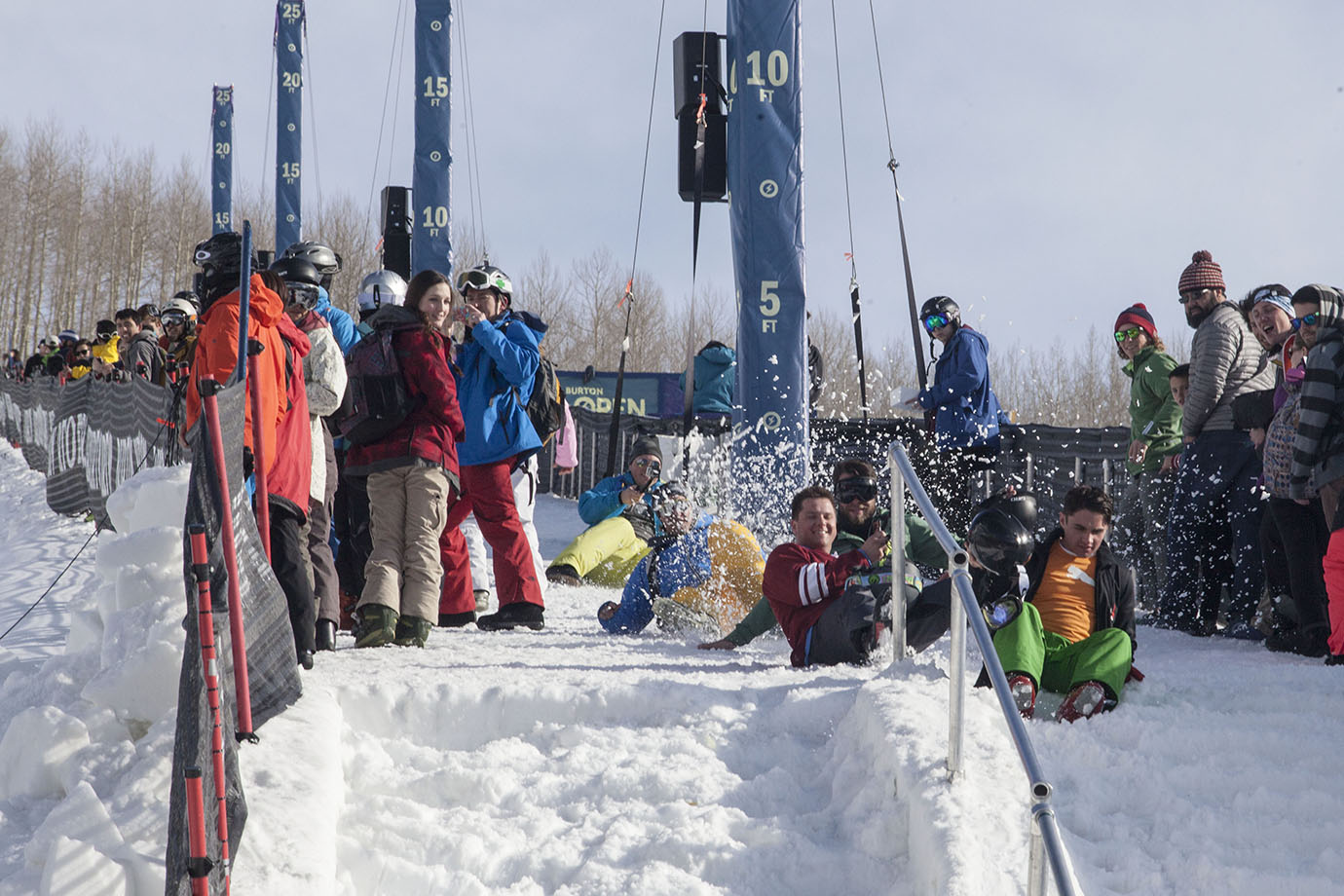 Spectators amuse themselves on the snow steps that lead up the left side of the superpipe wall, racing down on their backsides.