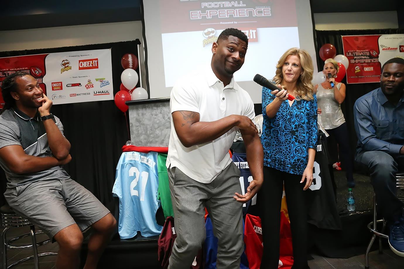 "LaDainian Tomlinson showcases his patented ""Electric Glide"" for host Tara Hitchcockas as Larry Fitzgerald and Michael Vick look on during the Kurt Warner Ultimate Football Experience Draft Party in Phoenix, Ariz."