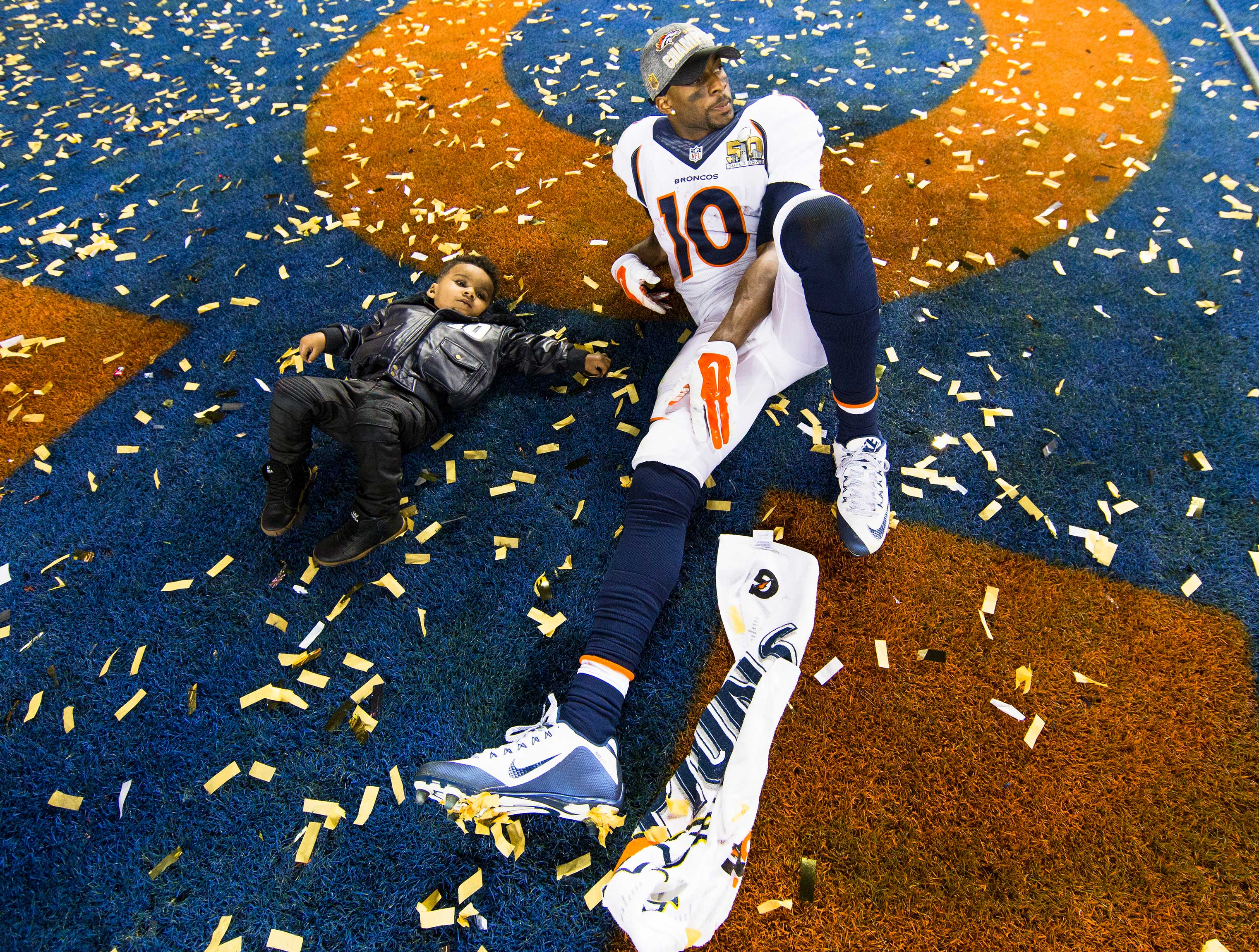 Emmanuel Sanders on the field with his son after the game.