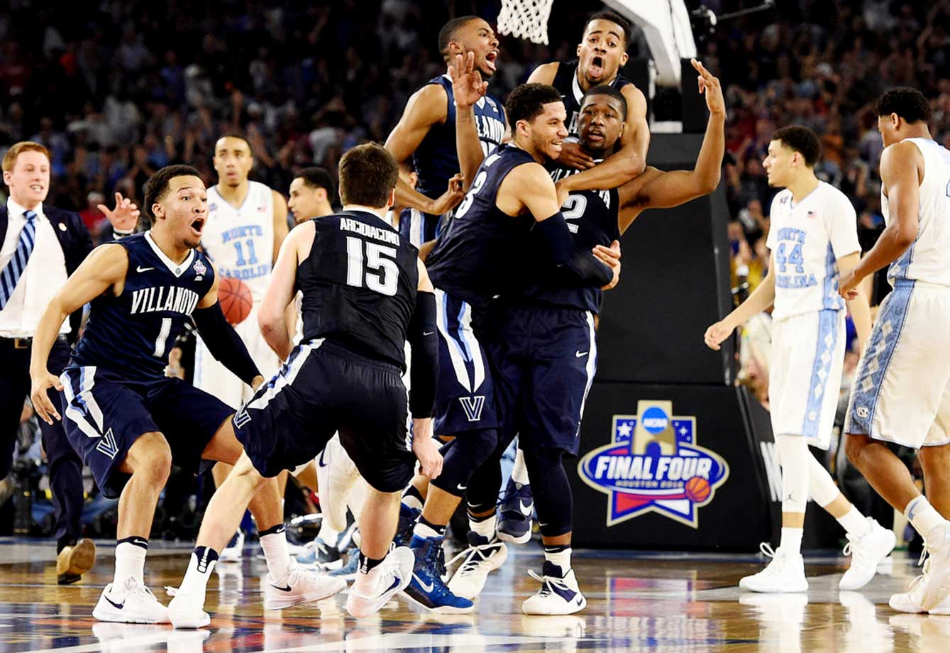 Kris Jenkins is mobbed by his Villanova teammates after his buzzer-beating three gave the Wildcats a 77-74 win over North Carolina.