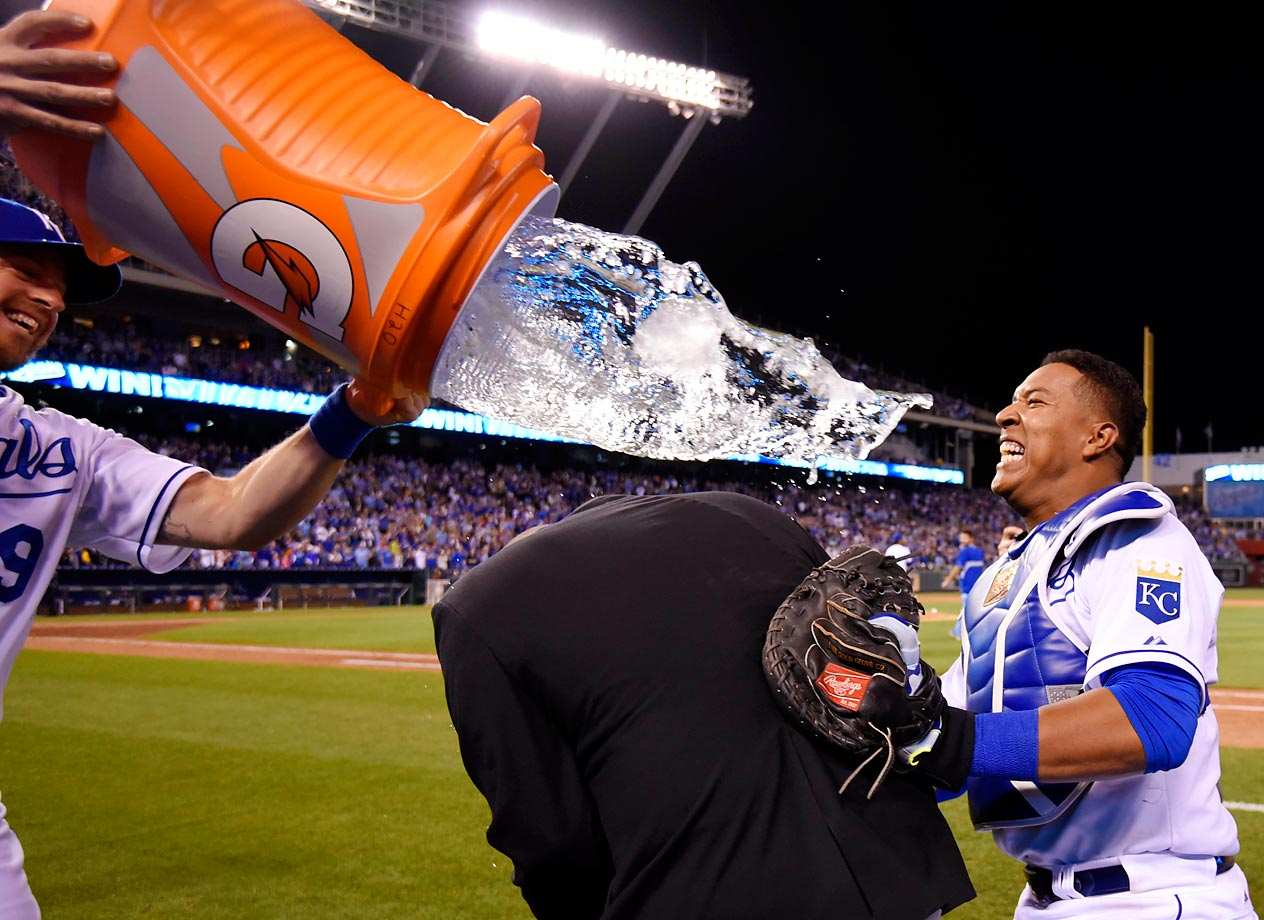Salvador Perez of the Royals takes cover to avoid being doused by Erik Kratz after a 4-1 win over the Tigers.