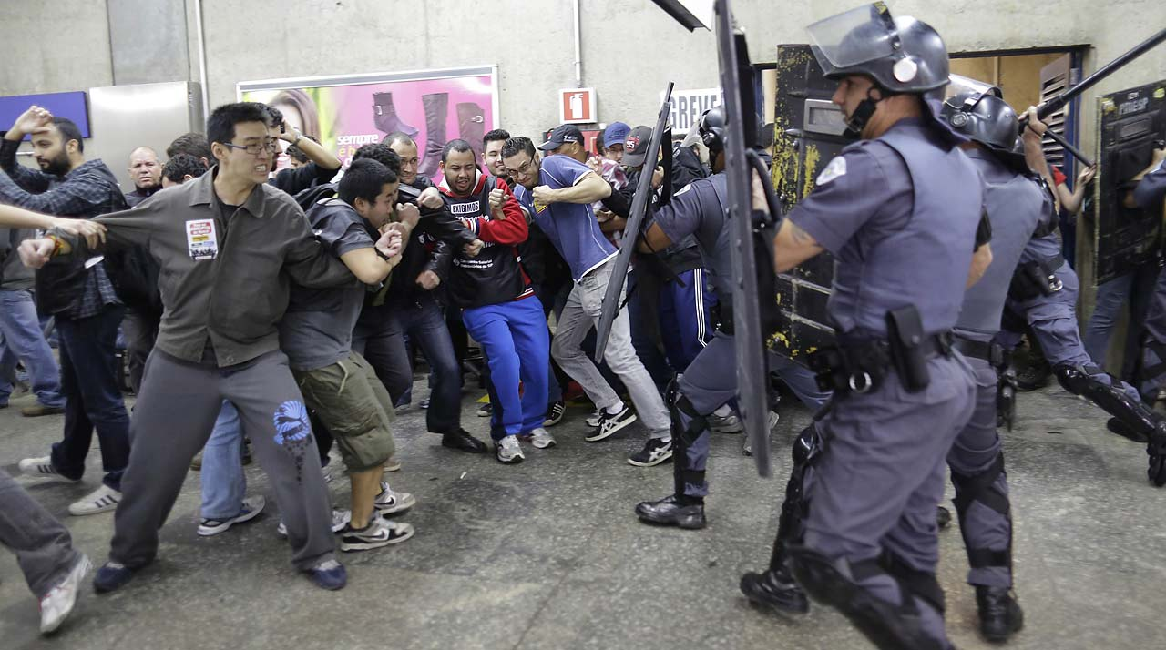 In this Friday, June 6, 2014 photo, subway train operators, along with some activists, clash with police at the Ana Rosa metro station on the second day of their metro strike in Sao Paulo. The workers clashed with police as they tried to block other operators from breaking the strike. Overland commuter train operators went on strike Thursday, putting at risk the only means that most soccer fans will have to reach Itaquerao stadium ahead of this week's World Cup.