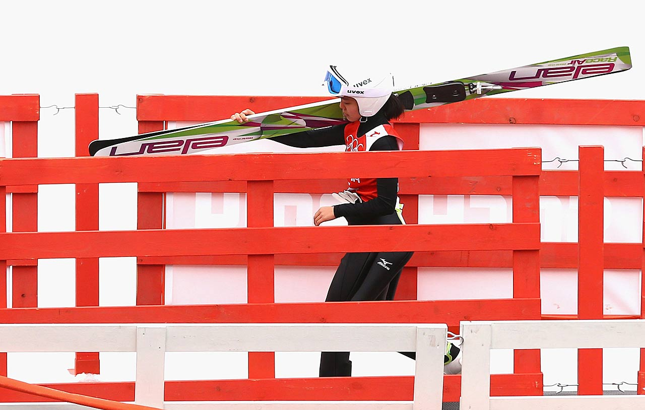 Sara Takanashi of Japan walks to the chairlift during the Ladies' Normal Hill Individual Ski Jumping training.