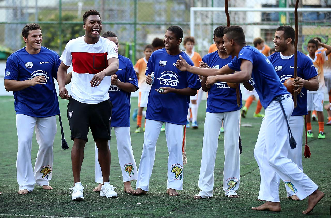 Daniel Sturridge laughs as he is invited to dance during a visit to Complexo Esportivo da Rocinha on June 9 in Rio de Janeiro.