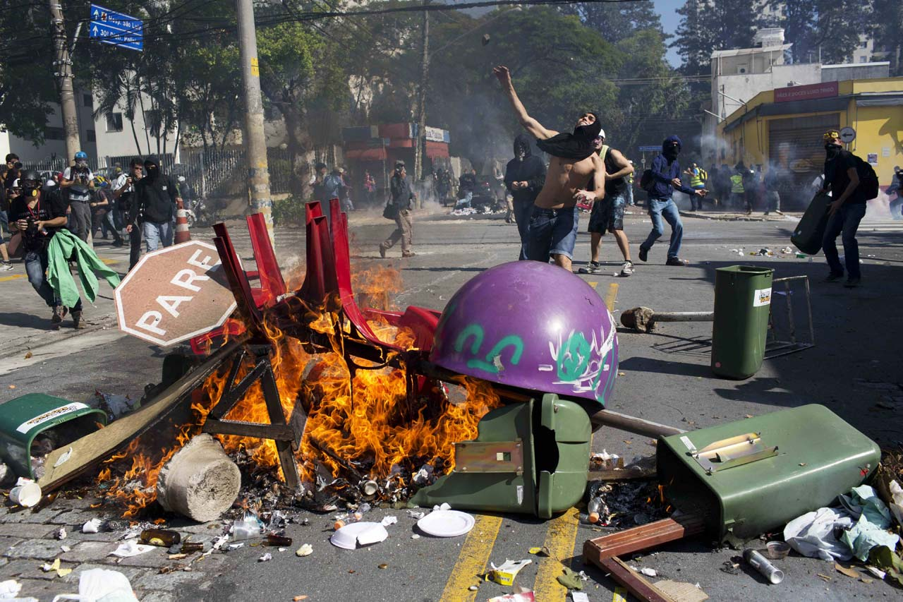 A masked man throws a stone towards riot policemen during a June 12 protest by people demanding better public services and against the money spent on the World Cup soccer tournament in Sao Paulo. Brazilian police clashed with anti-World Cup protesters trying to block part of the main highway leading to the stadium that hosts the opening match of the tournament.
