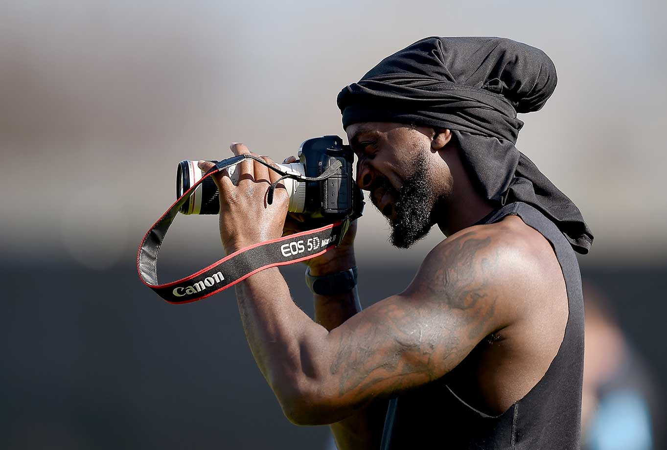 Injured player Charles Tillman of the Carolina Panthers takes photographs of his teammates in drills.