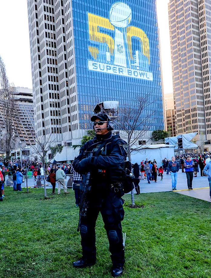 A heavily armed San Francisco police officer stands guard in Super Bowl City.