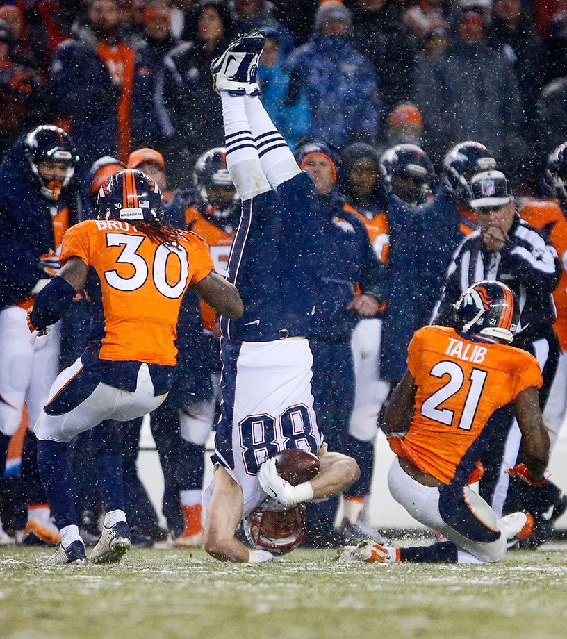 Scott Chandler of the New England Patriots gets flipped by Aqib Talib and David Bruton of the Denver Broncos.