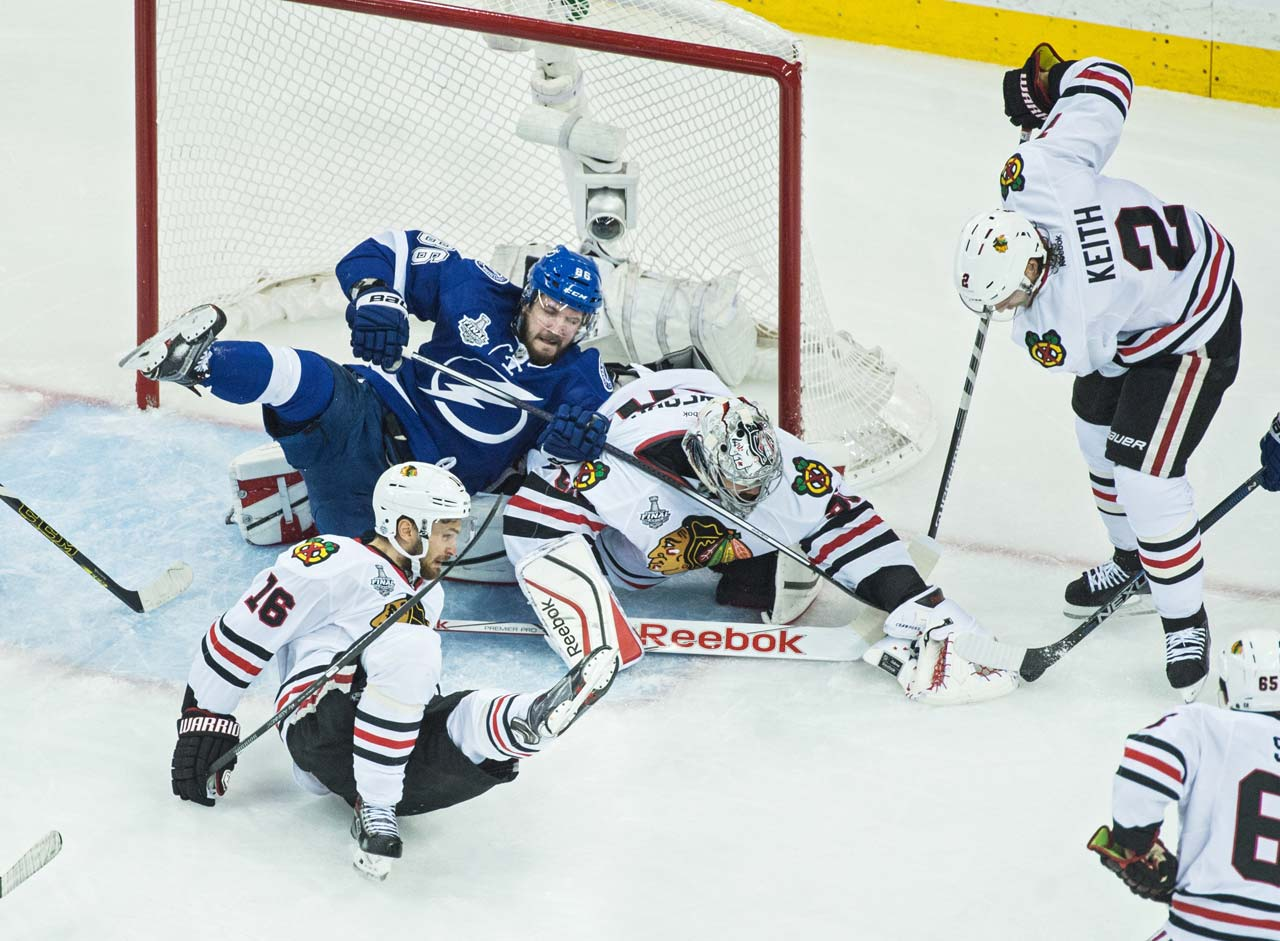 Corey Crawford (50) reaches for the puck as teammate Duncan Keith (2) aids in helping him clear it from the Blackhawks zone.