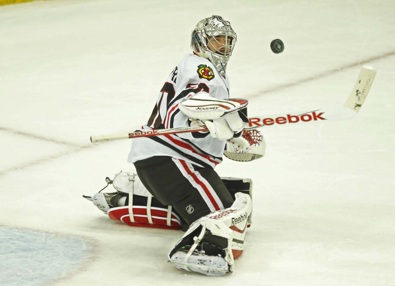 Corey Crawford watches as a puck soars through the air.
