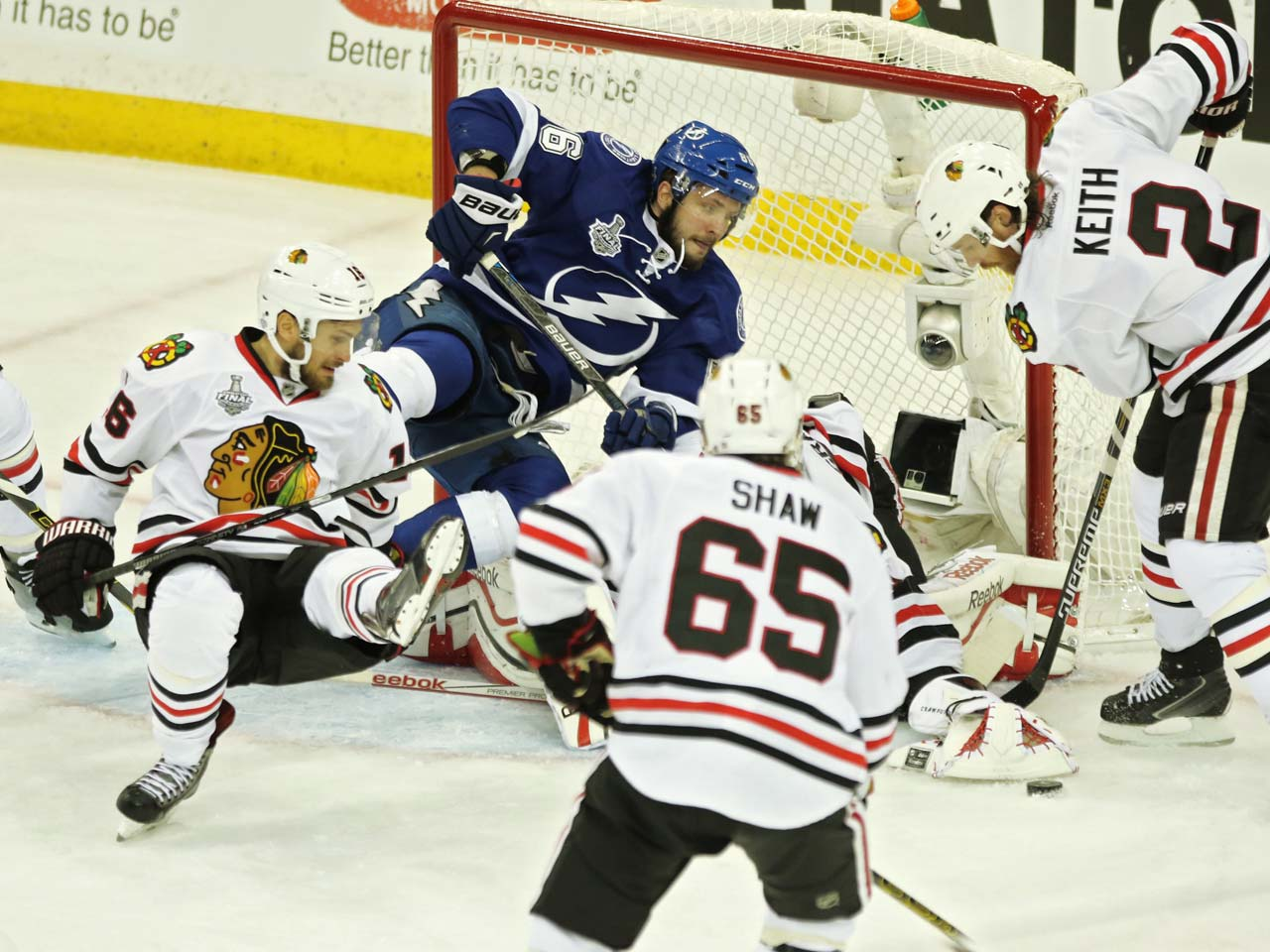 Corey Crawford (50) of the Blackhawks reaches to cover the puck as Duncan Keith (2) attempts to aid him in defending the Blackhawks net.