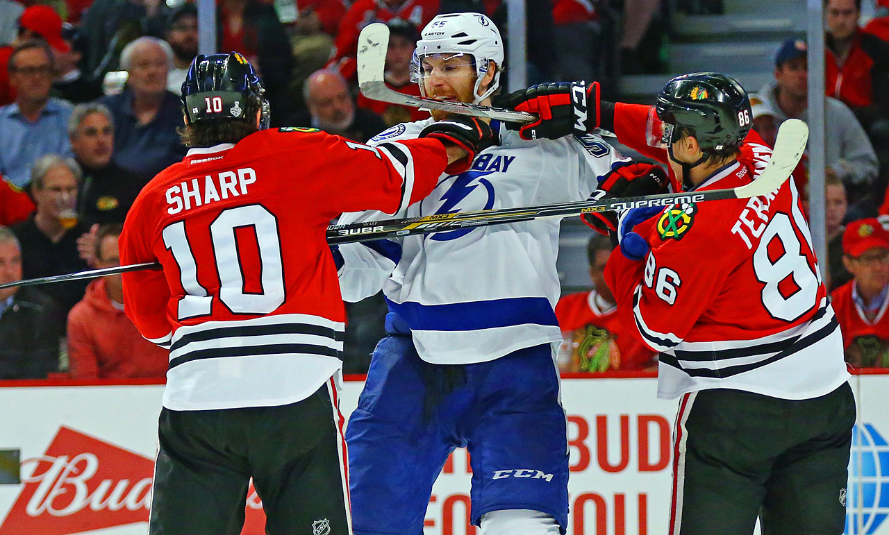 Braydon Coburn tries to deal with Patrick Sharp and Marian Hossa.