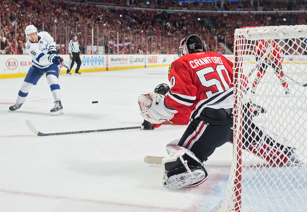 Anton Stralman shoots the puck on Corey Crawford.