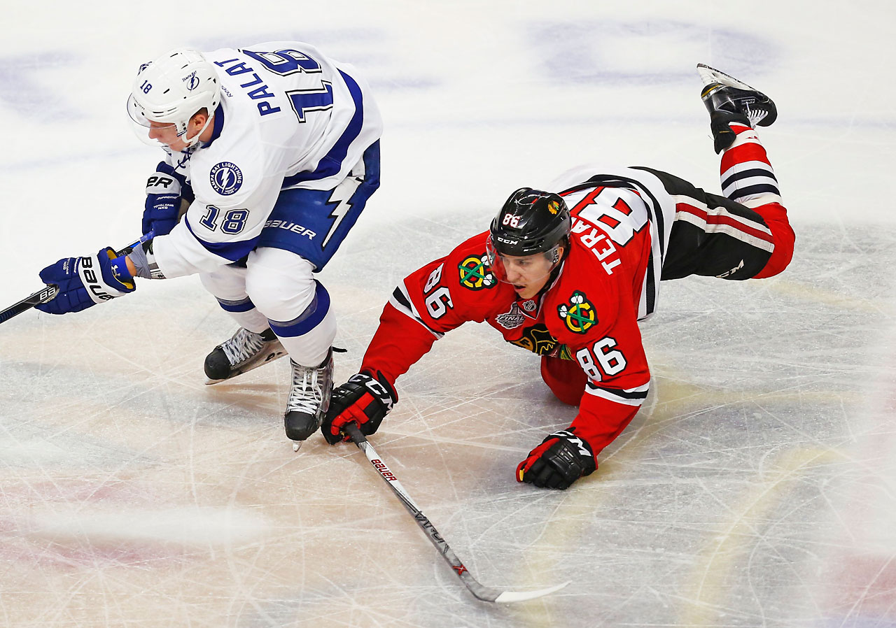 Teuvo Teravainen falls to the ice in an attempt to gain control of the puck.