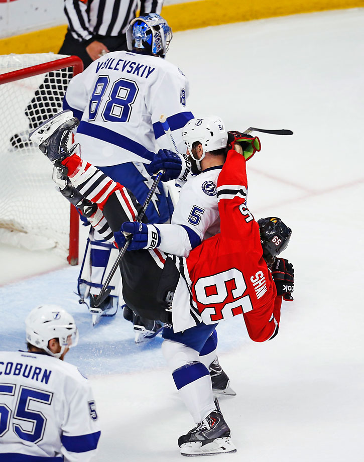 Jason Garrison of the Lightning checks Andrew Shaw to the ice in another tight matchup. All four games have been decided by one goal, the first time that has happened since 1968.