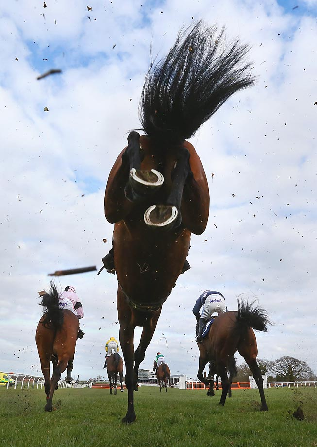 Horses clear a fence at the New Racing UK iPad App Handicap Steeple Chase at Wetherby Racecourse in England.