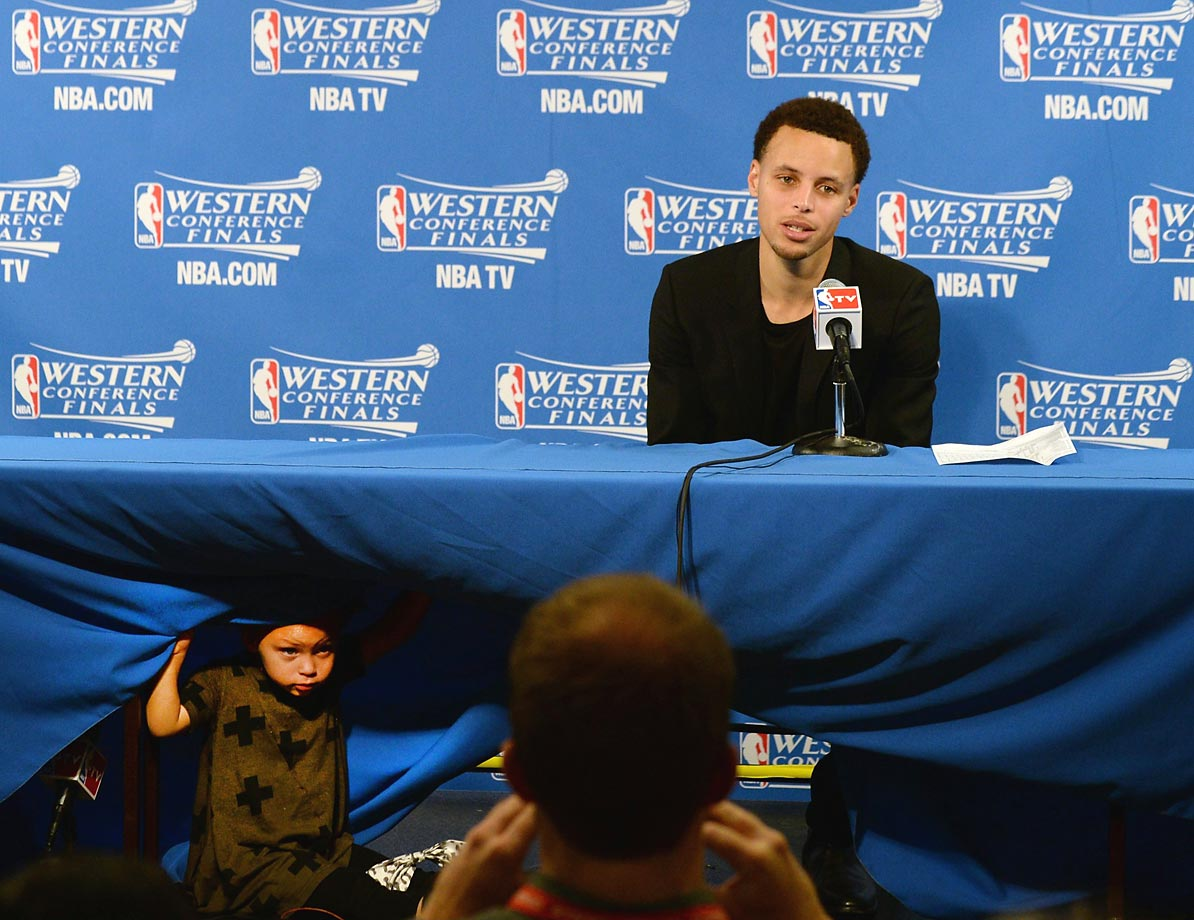 Stephen Curry's daughter, Riley, peeks out during the press conference after Game 1 of the Western Conference Finals.