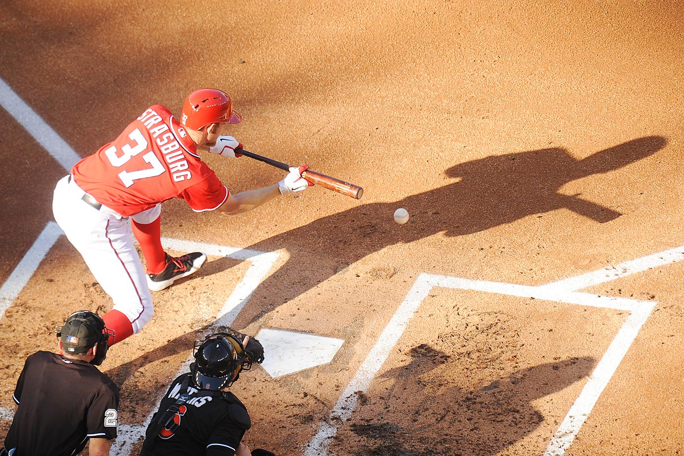Stephen Strasburg of the Washington Nationals bunts to score Bryce Harper during a game against the Miami Marlins.