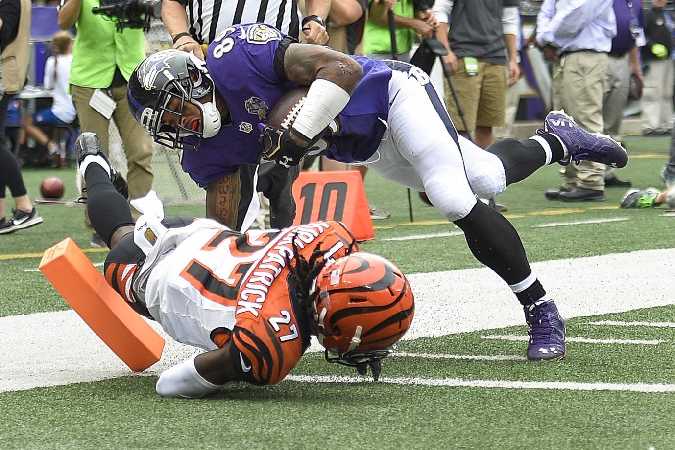 Steve Smith dives over Cincinnati cornerback Dre Kirkpatrick for a touchdown.