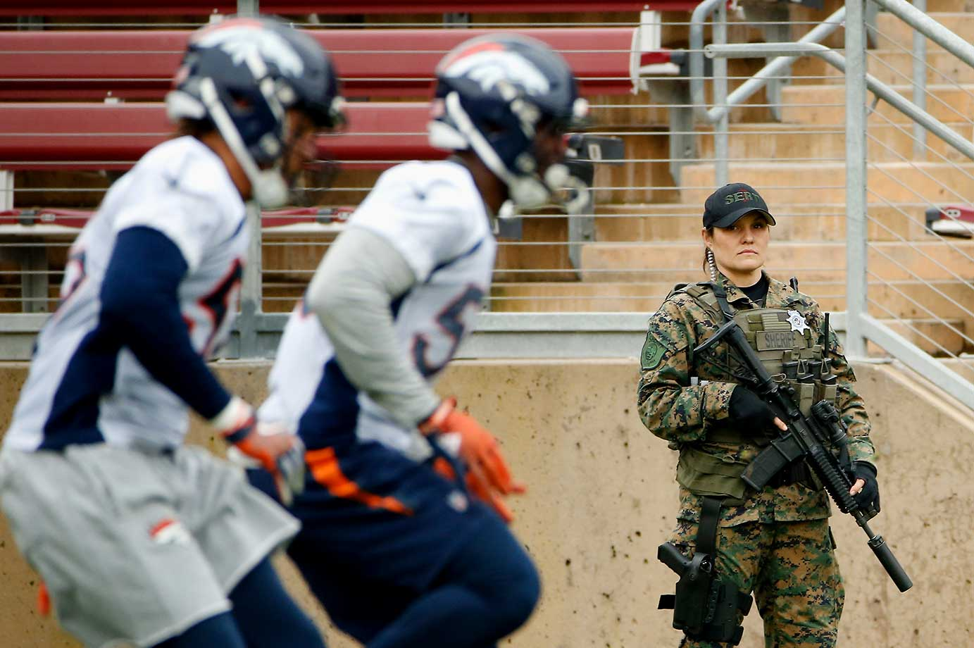 A security officer watches the Denver Broncos practice at Stanford University.