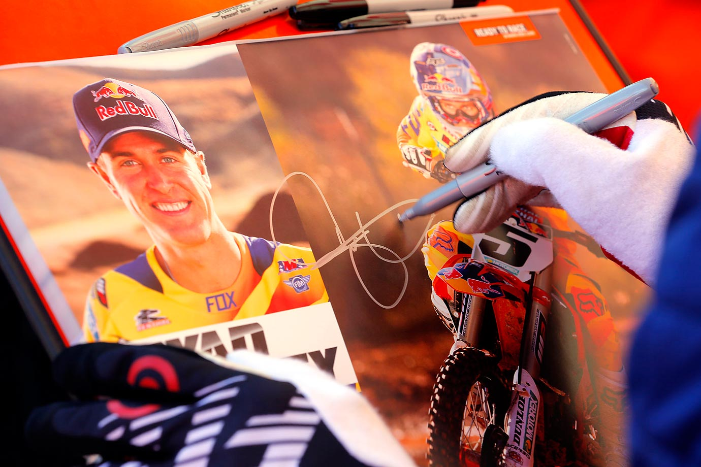 Dungey signs posters for fans at his pit during an autograph session.