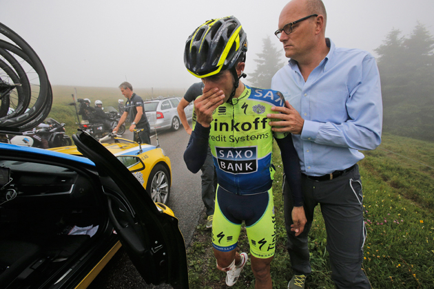 Spain's Alberto Contador abandons the race after crashing during the tenth stage of the Tour de France cycling race over 161.5 kilometers (100.4 miles) with start in Mulhouse and finish in La Planche des Belles Filles, France, Monday, July 14, 2014. At right is team manager Bjarne Riis of Denmark.