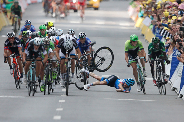 Andrew Talansky of the U.S. crashes as the pack with stage winner Italy's Matteo Trentin, foreground left, sprints towards the finish line during the seventh stage of the Tour de France cycling race over 234.5 kilometers (145.7 miles) with start in Epernay and finish in Nancy, France, Friday, July 11, 2014.