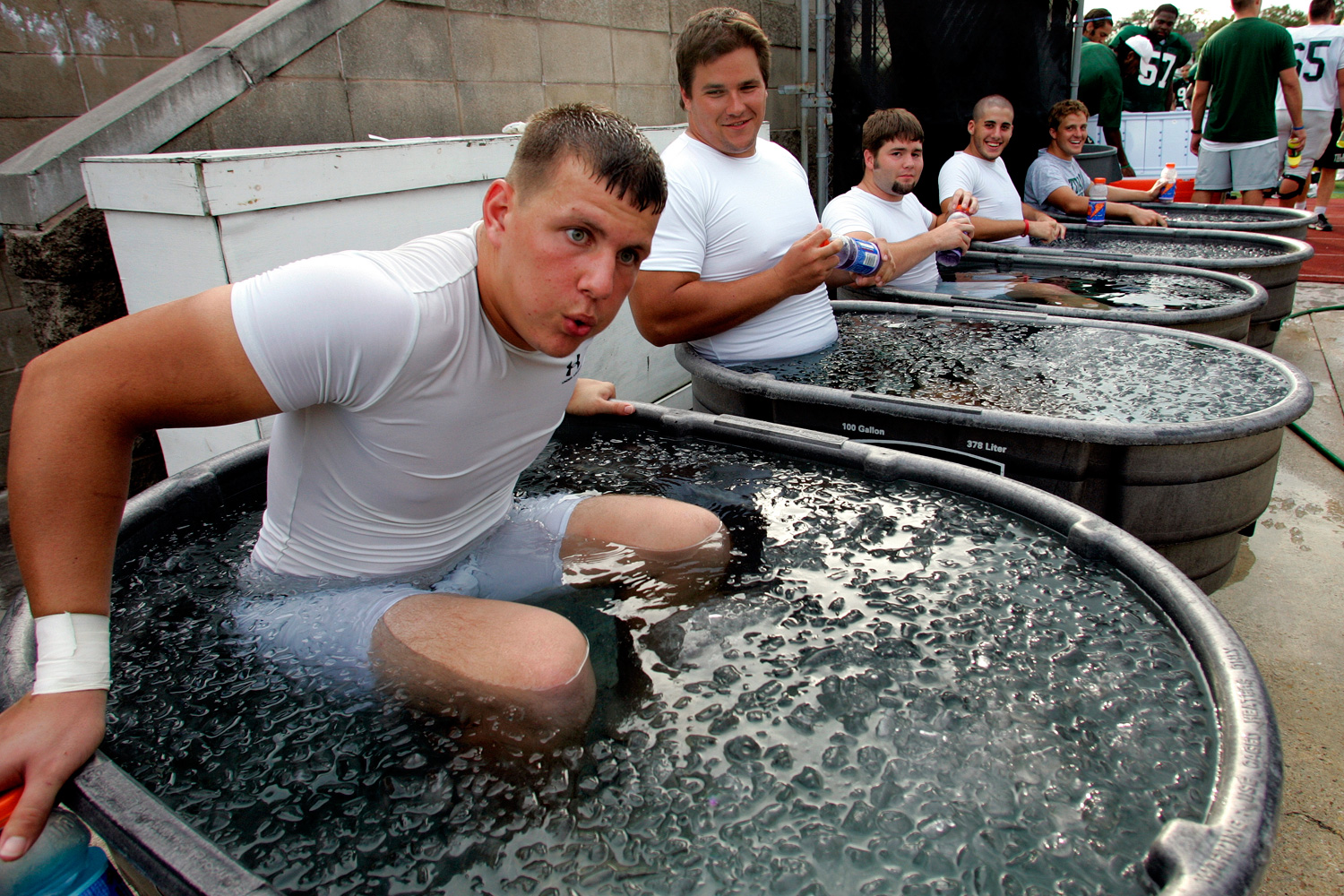 Tulane tight end Justin Kessler (L) takes his time getting into his ice bath after practice in New Orleans. The team has 14 tubs with four 40-pound bags of ice going into each tub, and more added as the players rotate into the bath for about five minutes.