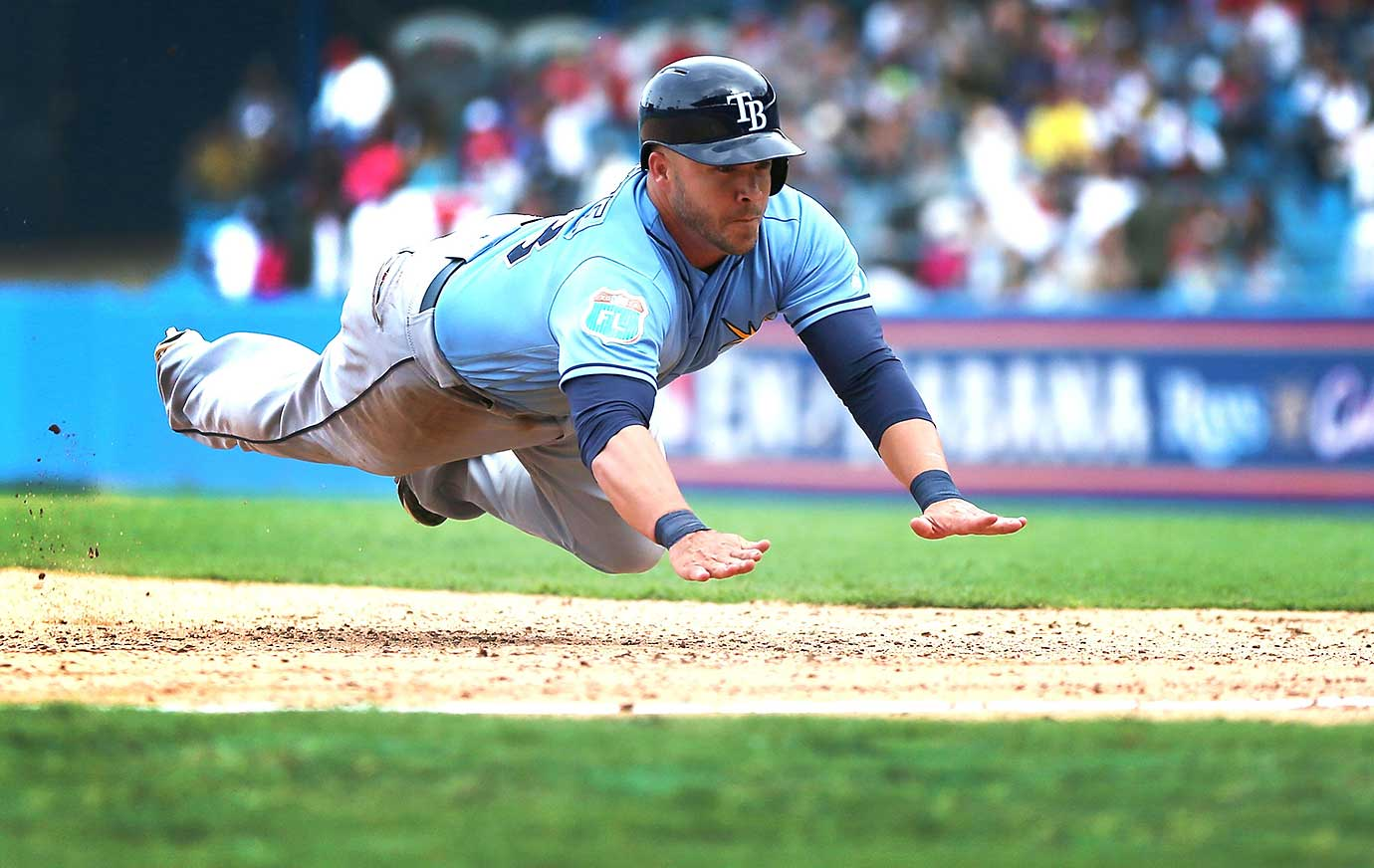 Steve Pearce of the Tampa Bay Rays dives safely into third base during the exhibition game in Cuba.