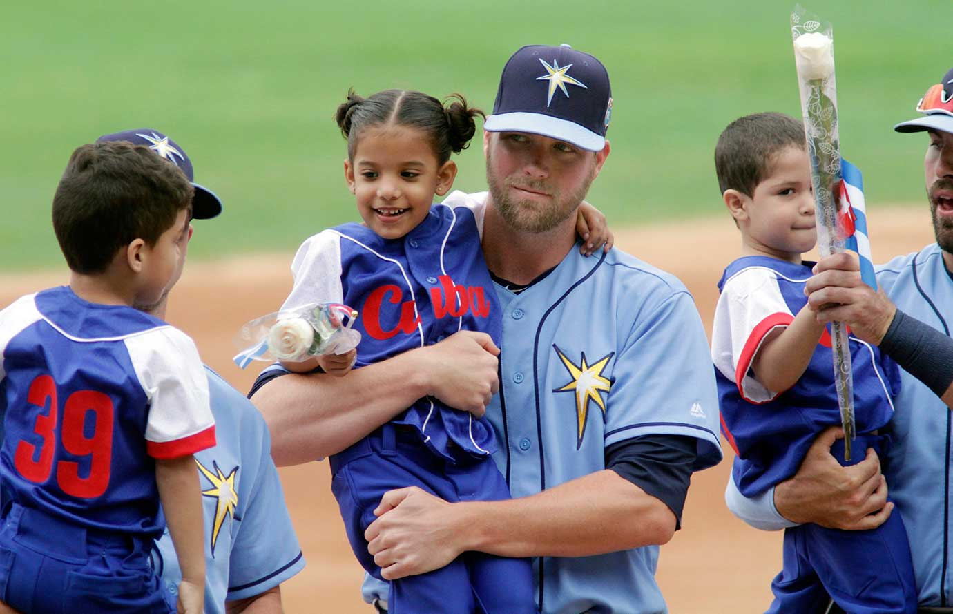 Here are some of the images that caught our eye on a day in which the Tampa Bay Rays made the first visit to Cuba by a major league team since 1999. In this photo, Rays pitcher Ryan Webb holds a Cuban child during introductions. President Barack Obama attended the game and is the first sitting president to have visited the communist island in 88 years.