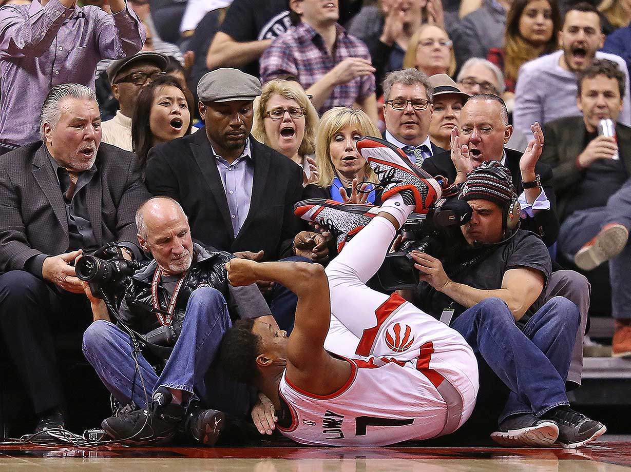 Retired heavyweight boxing legends Ceorge Chuvallo and Lennox Lewis watch Kyle Lowry of Toronto tumble into the sidelines.
