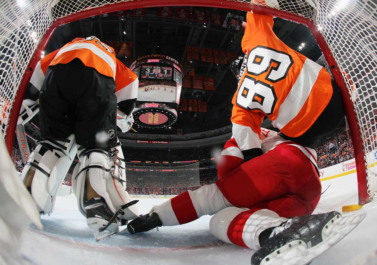 Henrik Zetterberg of the Red Wings crashes into the net of Steve Mason of the Flyers along with Sam Gagner.