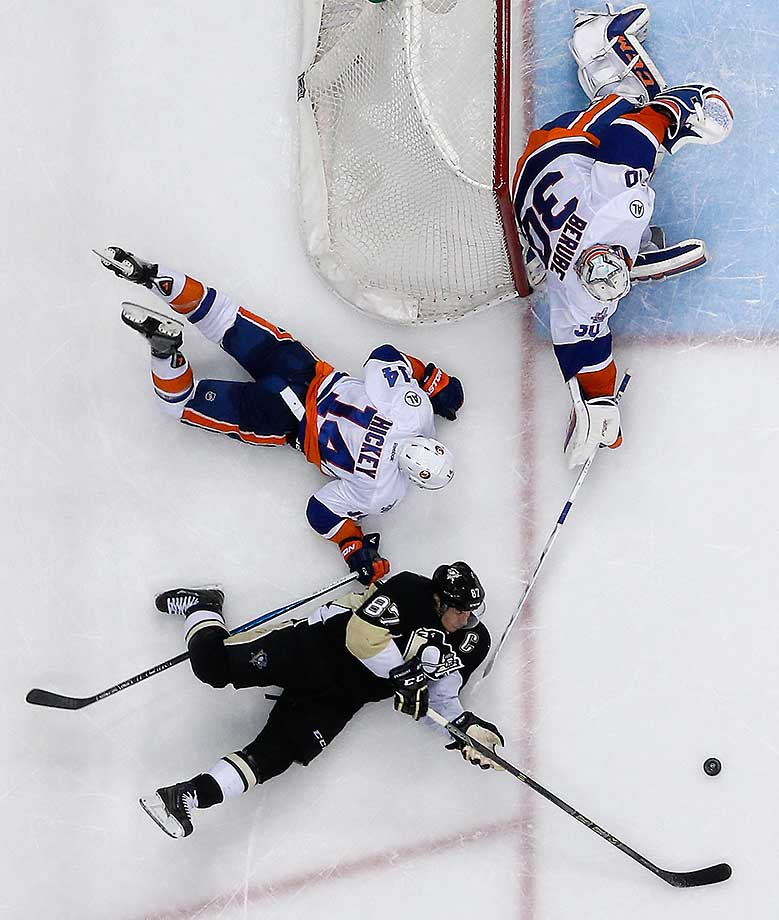Islanders goalie Jean-Francois Berube can't clear the puck before Pittsburgh's Sidney Crosby gets off a pass after attempting a wrap-around against Thomas Hickey. The Penguins won 2-1 in a shootout.