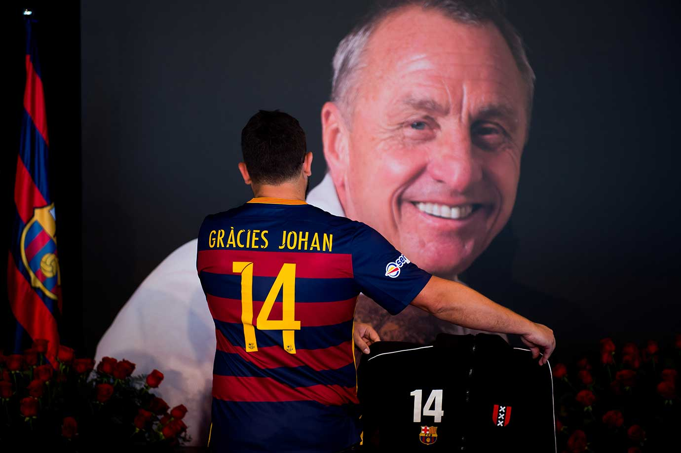 A supporter wearing a FC Barcelona shirt with a message saying 'Thanks Johan' in catalan pays tribute to late Dutch football star Johan Cruyff in a special condolence area set up at Camp Nou stadium in Barcelona, Spain.