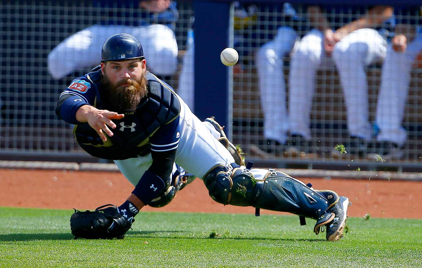 San Diego catcher Derek Norris tosses the ball to pitcher Colin Rea covering home plate after a pitch got away from Norris.