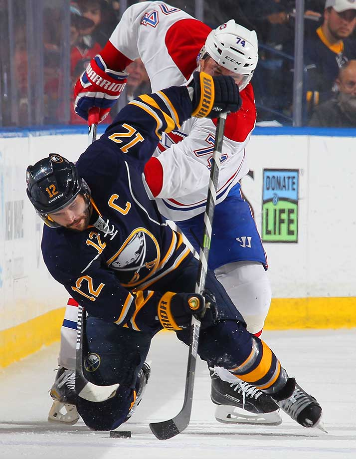 Brian Gionta of the Buffalo Sabres battles for the puck against Alexei Emelin of the Montreal Canadiens.