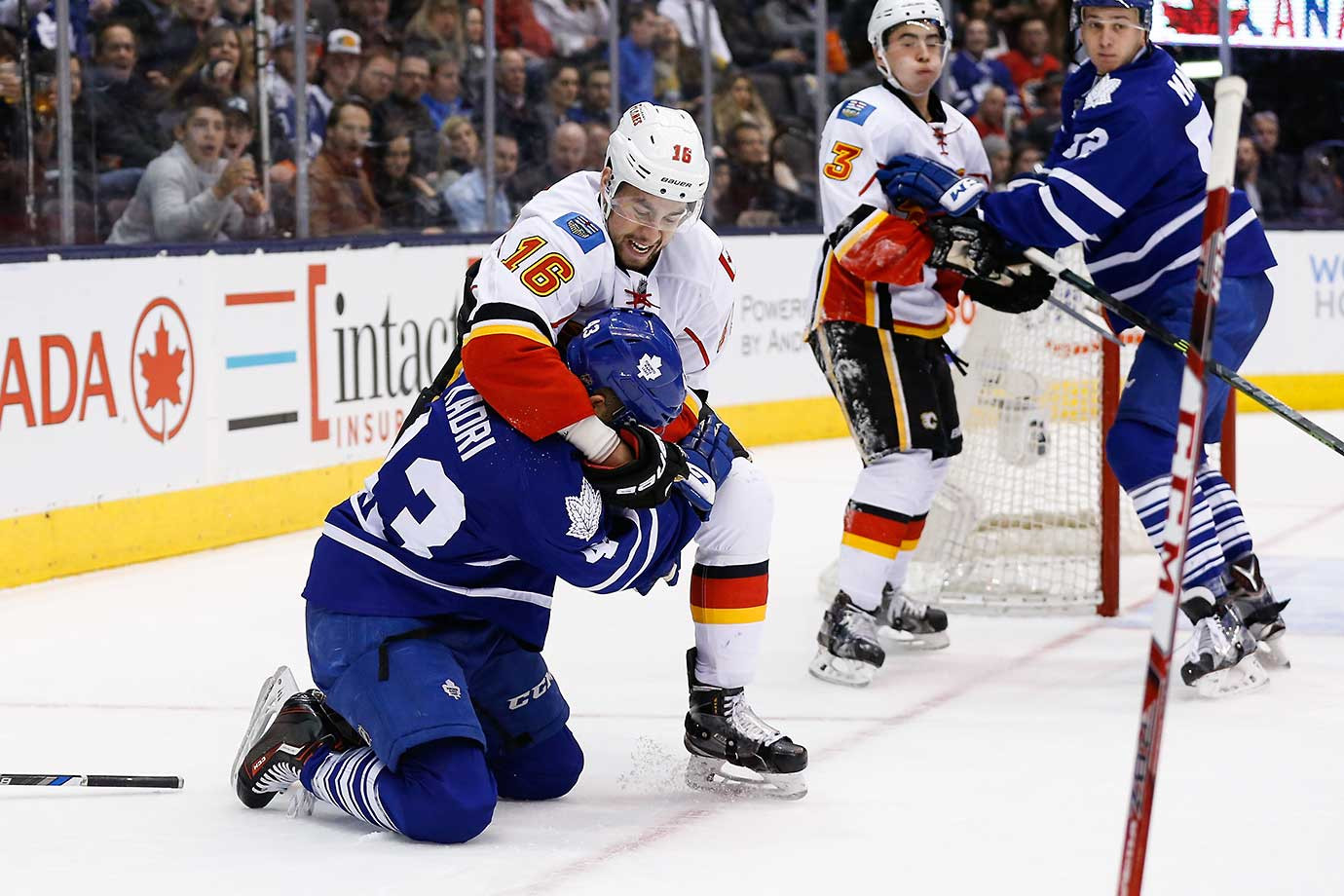 Calgary's Josh Jooris puts Toronto Maple Leafs center Nazem Kadri into a headlock.