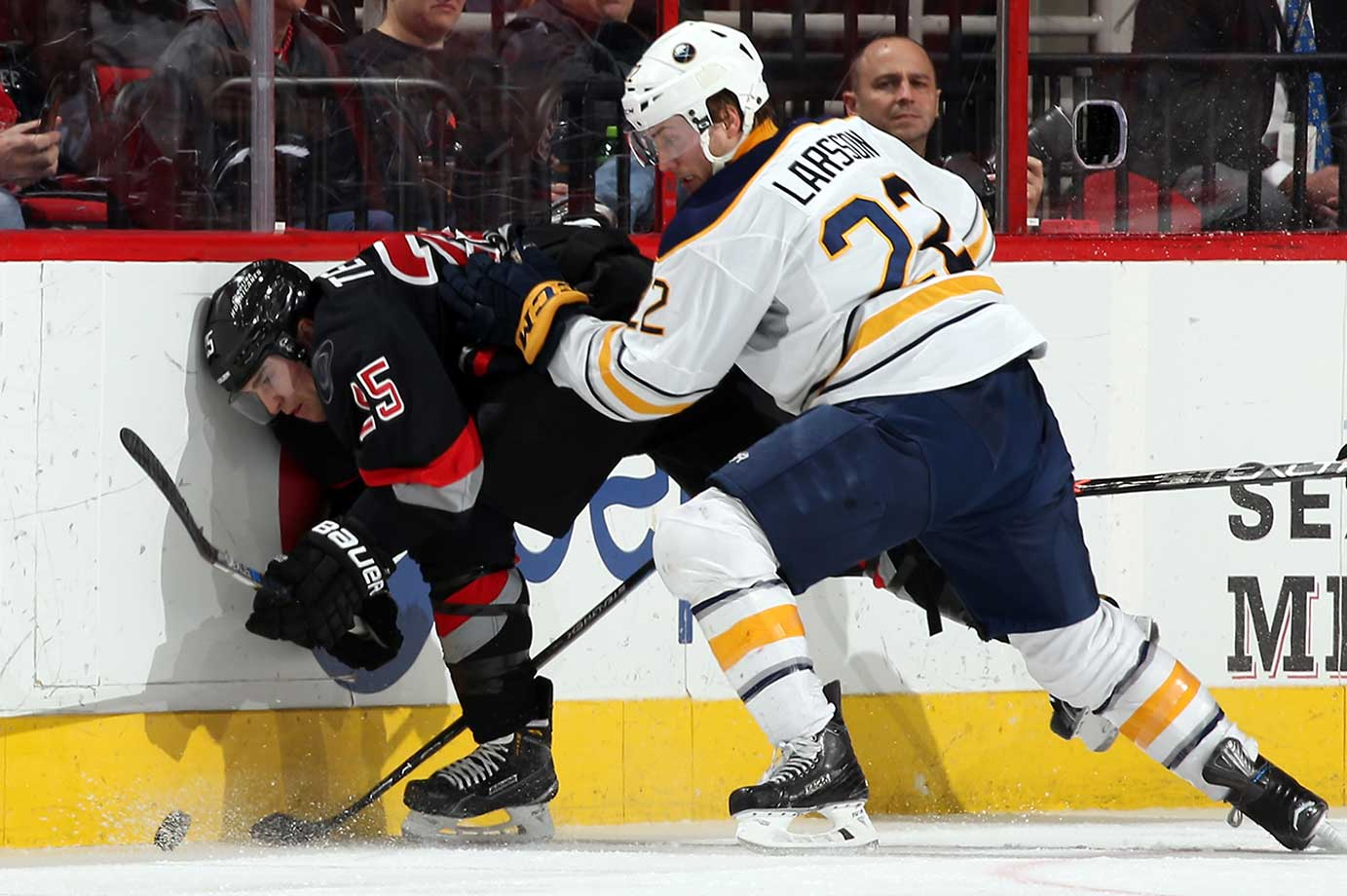 Johan Larsson of the Buffalo Sabres knocks Chris Terry of the Carolina Hurricanes off the puck.