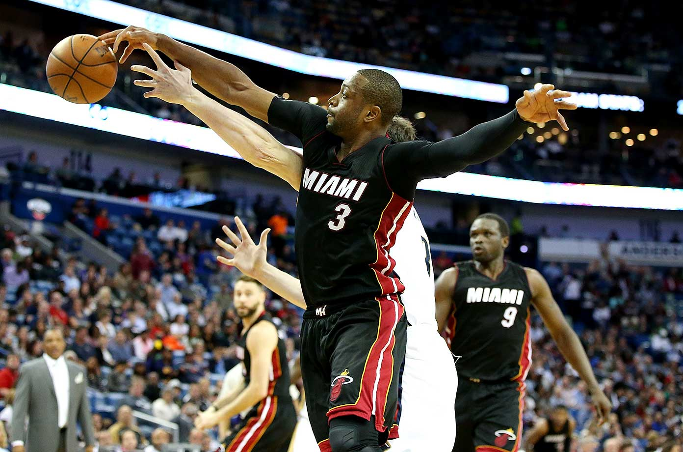 Dwyane Wade of the Miami Heat fights for a loose ball with Omer Asik of the New Orleans Pelicans.