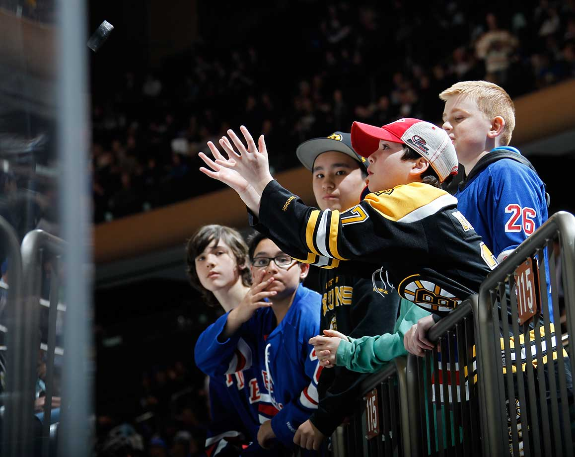 A young Boston Bruins fan catches a puck after it was tossed to the crowd by Lee Stempniak.