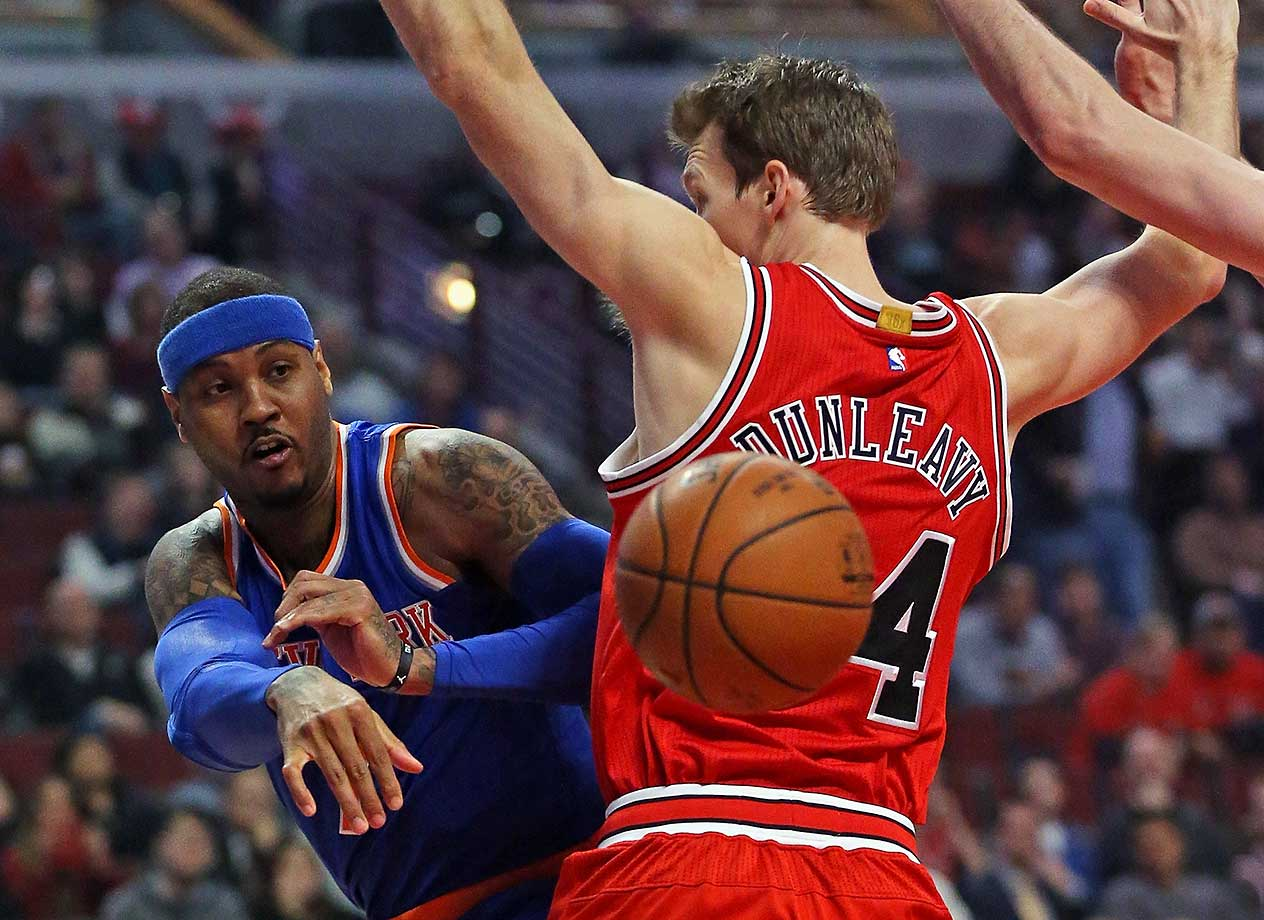 Carmelo Anthony of the New York Knicks passes around Mike Dunleavy of the Chicago Bulls.