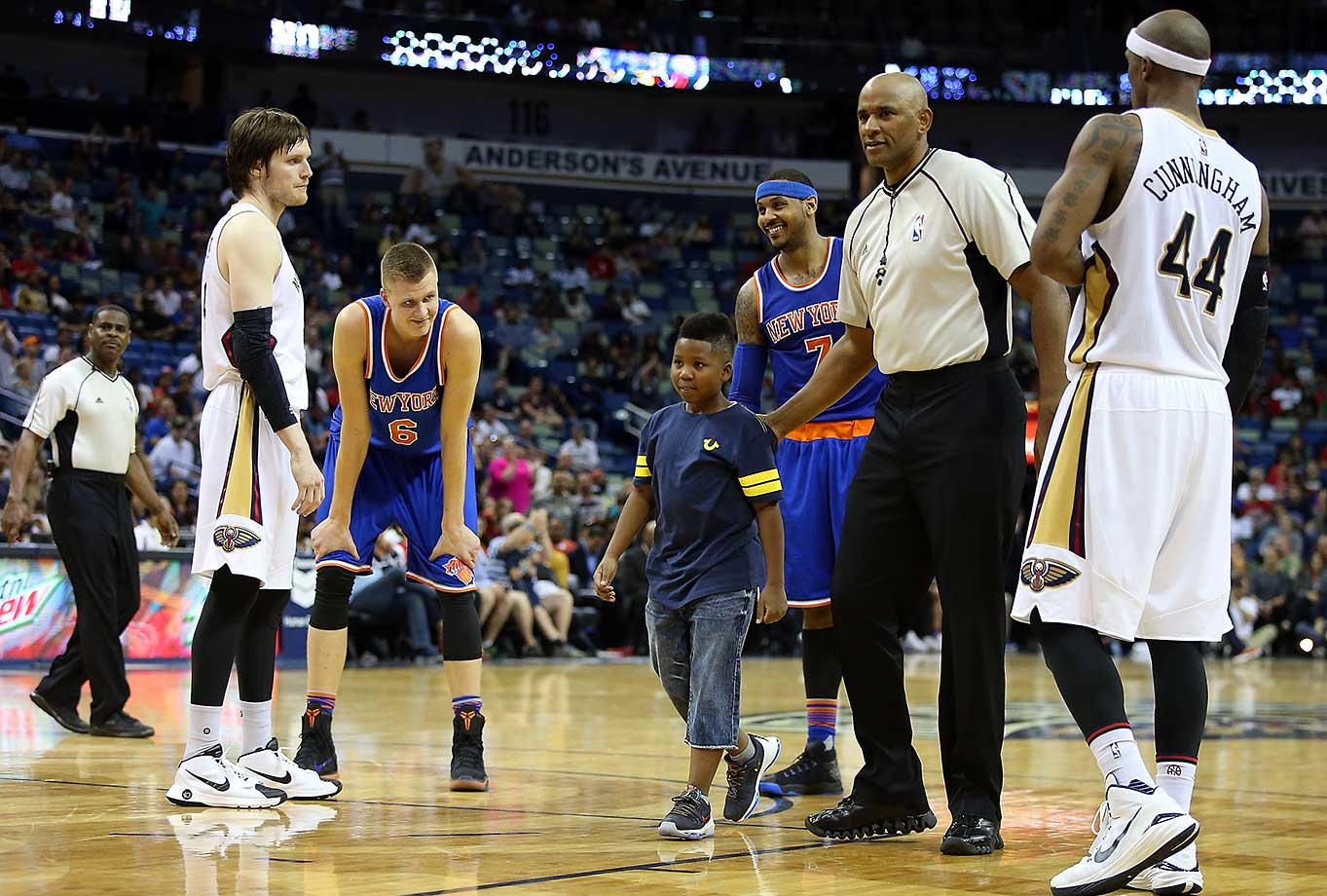 A young boy is escorted off the court after running out there to hug Carmelo Anthony of the Knicks during a game against New Orleans.