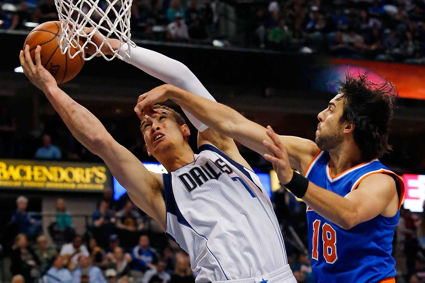 Dallas Mavericks' Dwight Powell shoots a layup while fouled by Sasha Vujacic of the Knicks.